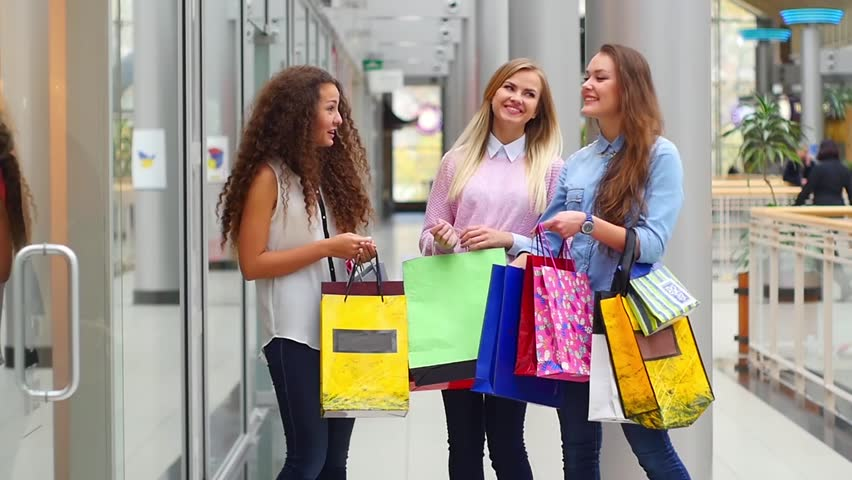 Two Beautiful Girls With Shopping Bags Come Out Of The Store In ...