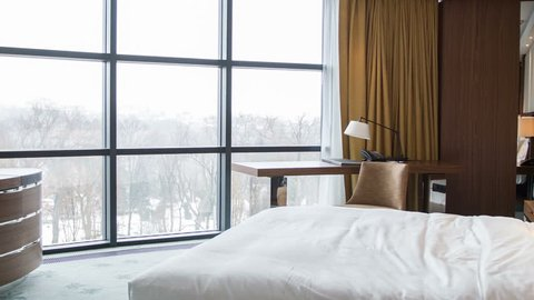 Elegant room with spectacular winter view. Shot entering a luxurious hotel bedroom.