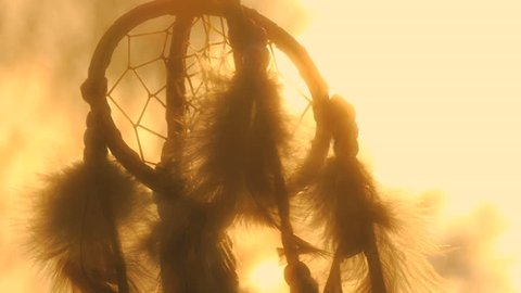 Native American dreamcatcher hanging in breeze at sunset, slow zoom into sun flare