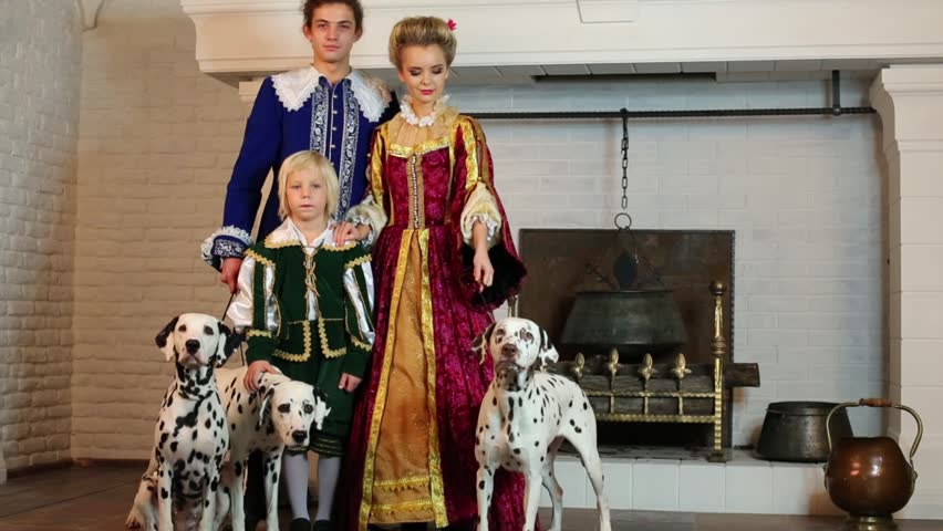 Father, mother and happy little son in medieval costume stand near fireplace with three dalmatians on leashes