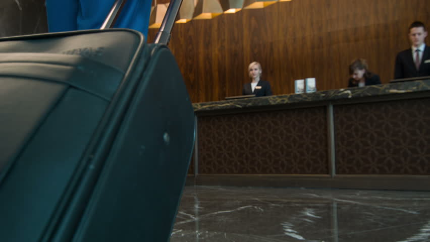 Arrival to hotel. New visitor with luggage coming to reception of five-star hotel to register and get key of his room