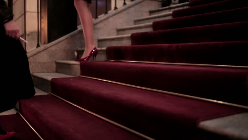 The stairs paved with red carpet. On the red carpet are women. Female feet close up / Women's feet are on the red carpet.