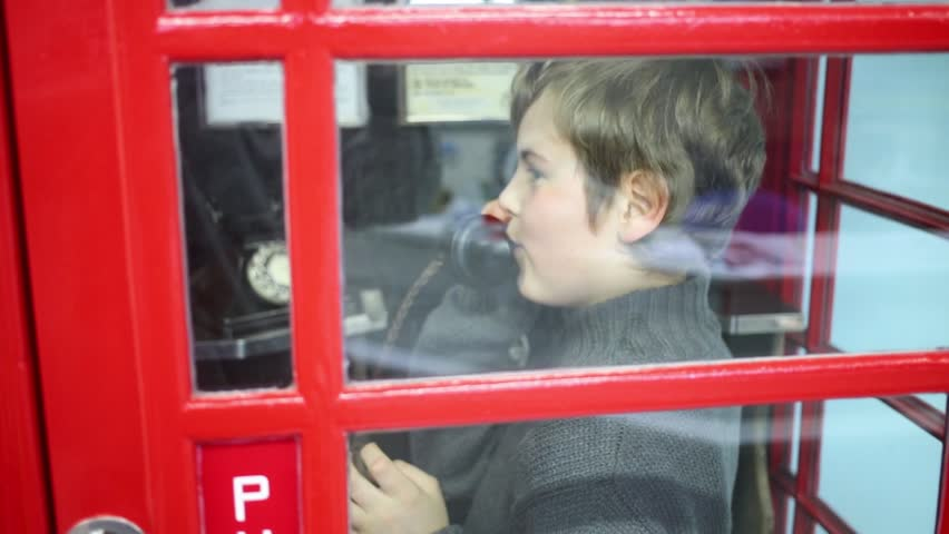 MOSCOW, RUSSIA - APR 5, 2014: Boy in grey talks phone in red telephone box in Museum of phone in Preobrazhenskoe district