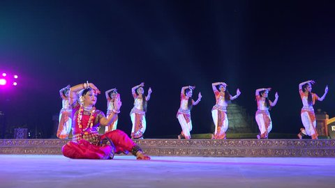 KONARK, INDIA - 3 DECEMBER 2014: Dancers wearing traditional dresses hold a classic performance on stage, during the Konark Dance Festival in India.