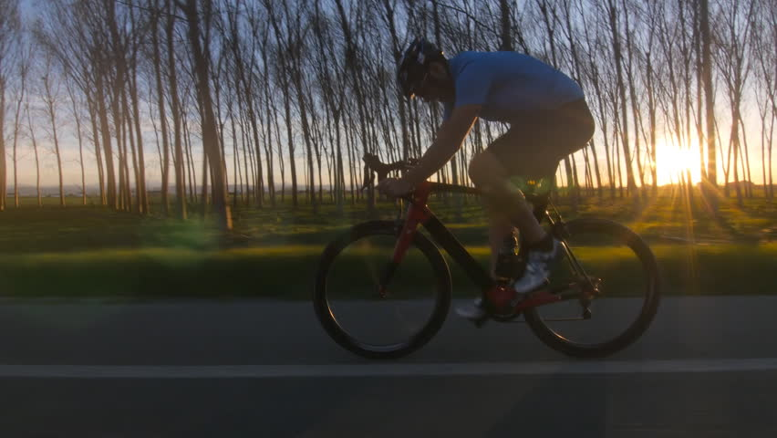 bf1145a4fea healthy man riding bicycle working out. fitness outdoors at the sunset. 4k  tracking shot from camera car