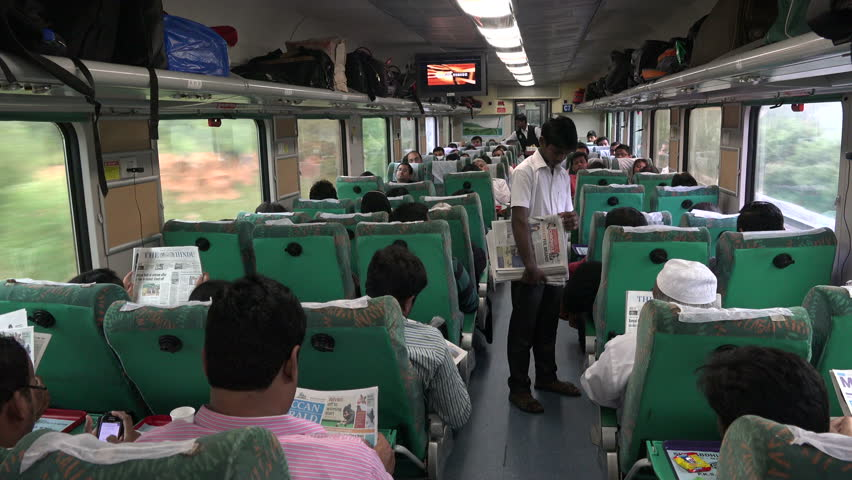 BANGALORE TO CHENNAI TRAIN, INDIA - 20 NOVEMBER 2014: An unidentified worker hands out free newspaper in the express train from Bangalore to Chennai, in India.