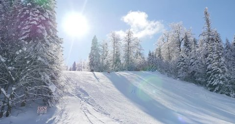 A 4K shot of a beautiful winter scene with some skiers skiing downhill/I´m having fun at the mountain