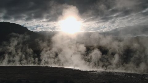 Spring with natural thermal water produce hot steam at sunrise at the famous El Tatio geyser valley at 4320 meters above sea level, Chile.