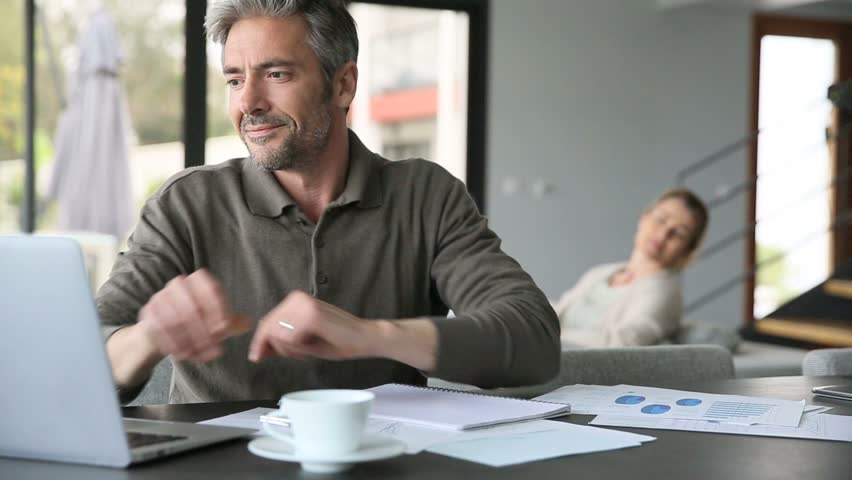 Man drinking coffee in front of laptop at home