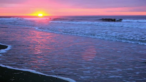 Beach sunrise.  Sun is at the horizon with waves and shore showing.  Pretty pinks, grays and purples in the sky, sea and shore and very nice reflections.