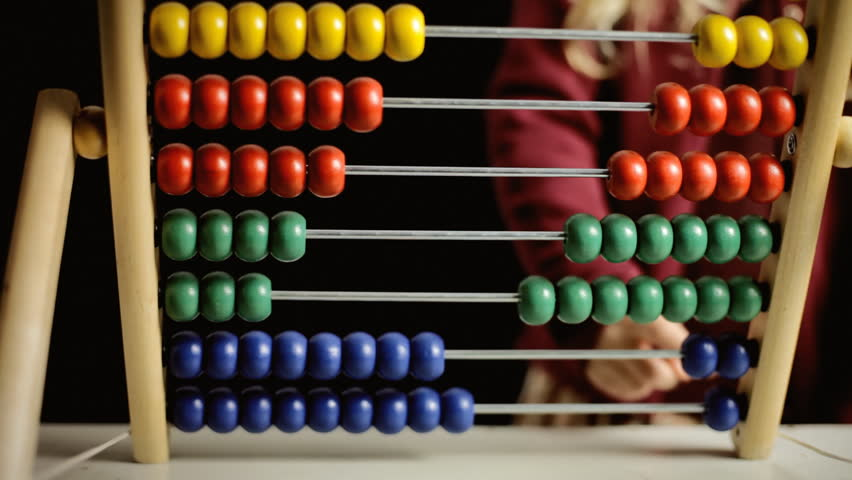 A cute little girl playing with an abacus, learning to count. Front view, detail of the beads being moved.