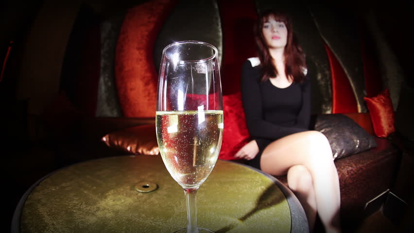 beautiful classic pinup girl in a VIP club drinking champagne