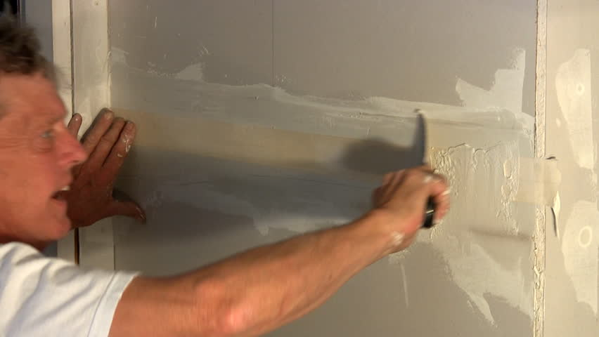 Bathroom Joint Compound putting ceramic tile on the wall. ceramist is slowly laying