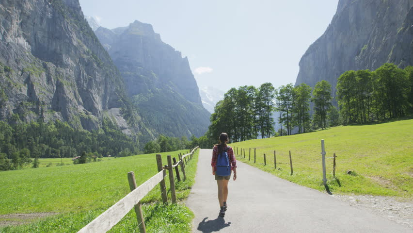People walking in Switzerland alps. Woman hiker tourist hiking on hike in Swiss alpine nature landscape in Lauterbrunnen valley in Bernese Oberland, Schweiz, Europe. RED EPIC SLOW MOTION.
