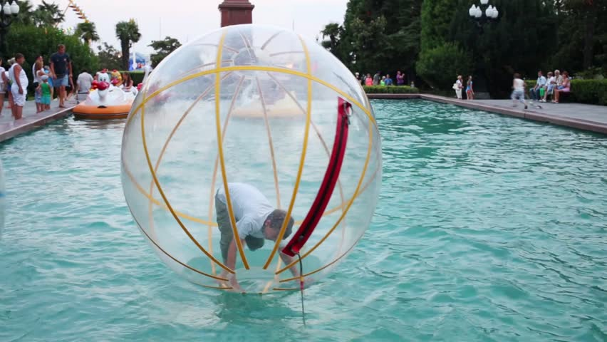 Boy teen flounders in large inflatable ball on water in pond