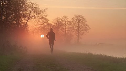 Man (silhouette) running on a gravel road during a foggy, spring sunrise in the beautiful countryside.