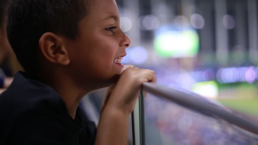 Cute shot of a beautiful child watching a game from the stands at a stadium