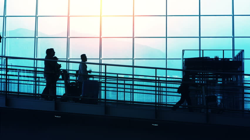 Sunset Silhouettes of Travelers in Airport. Sunset airport terminal hall. Walking travelers silhouettes.  | Shutterstock HD Video #9709913