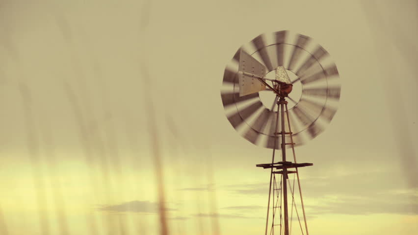 Vintage running farm windmill at sunset. Green alternative wind energy background with change of focus.