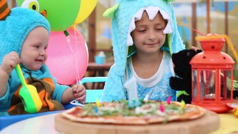 Brother And Sister In Costumes Of Monsters Play With Dog Toy Cafe Pizza