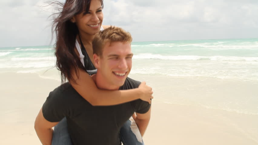 Young woman riding on young man's back