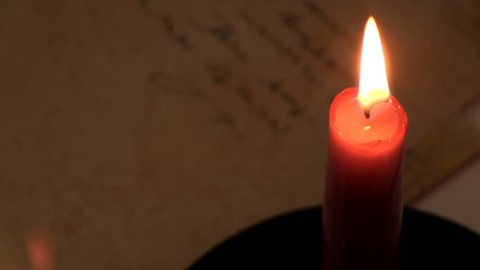 Handwriting a letter to secret lover by candlelight.