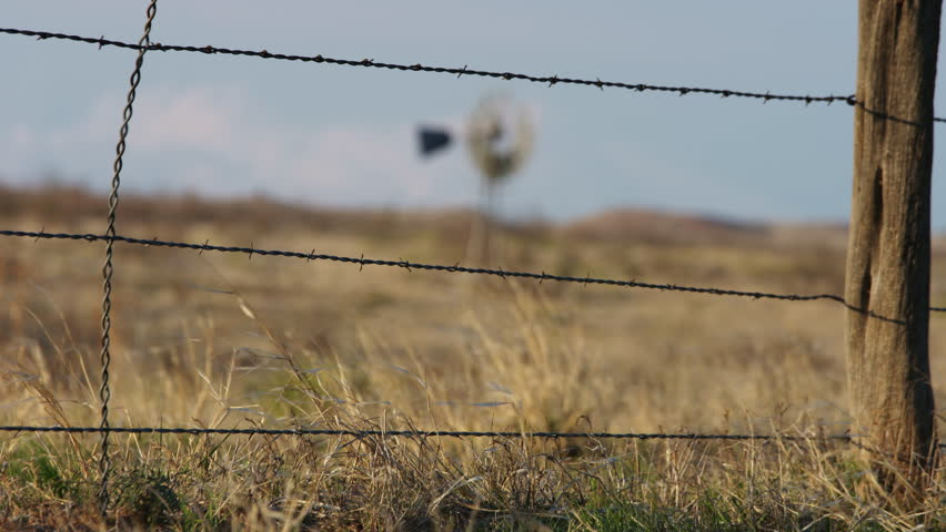 4k Video of an old Windmill focus pull from barbed wire fence, slow motion, wind blowing the grass in the desert of New Mexico #9747566