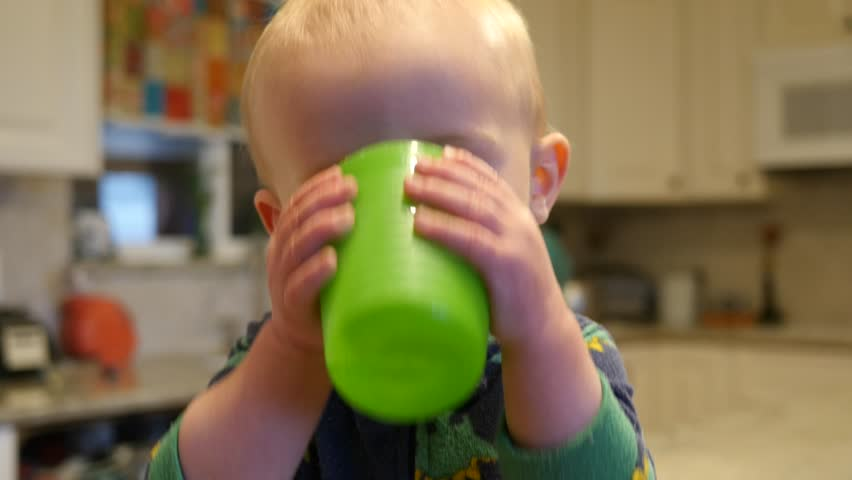 Cute baby playing with his glass of water spitting the water back out. cup covers most of his face.