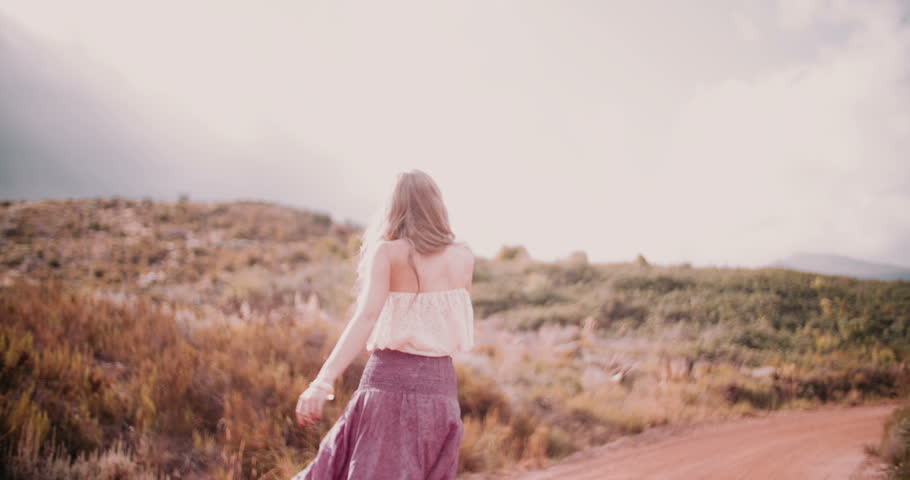 Boho girl dancing joyfully on a country dirt road in a summer landscape, Slow Motion