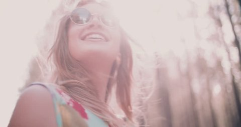 Happy boho girl laughing while walking in a summer forest