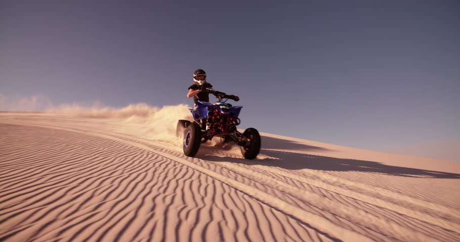 Competitive quad bike racer kicking up sand and dust while travelling up a sand dune, Panning in Slow Motion | Shutterstock HD Video #9774893