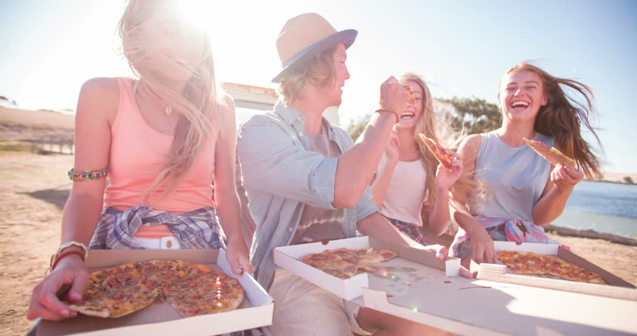 Teen friends sitting outside enjoying pizza and laughing together on a bright summer day