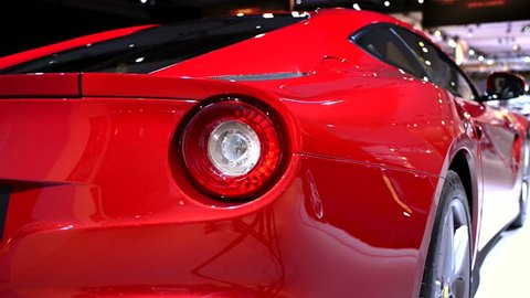 AMSTERDAM, THE NETHERLANDS - APRIL 16, 2015: Ferrari F12 Berlinetta V12 sports car close up at the 2015 Amsterdam motor show. The camera is sliding from left to right.