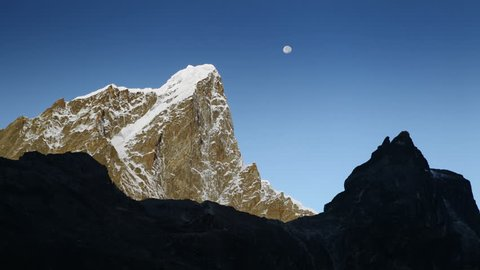 Time-lapse of the moon passing by Himalayan peaks at sunrise. The peaks and cliffs of the mountains are gradually illuminated by the rising sun.