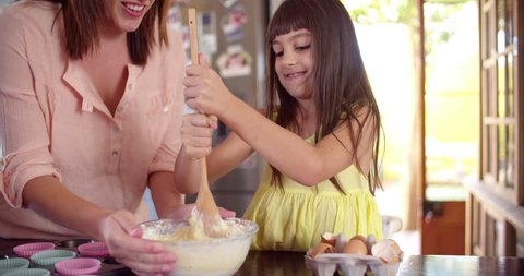 Little girl helping her mom in the kitchen by stirring the ingredients for their cake with a wooden spoon