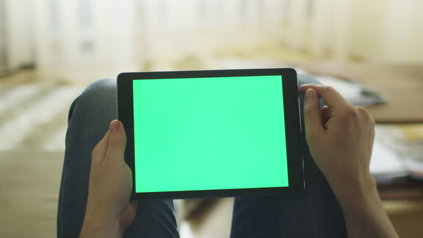 Man is Laying on Couch at Home and Using Tablet with Green Screen in Landscape Mode on Lap. Shot on RED Cinema Camera in 4K (UHD). | Shutterstock HD Video #9798848