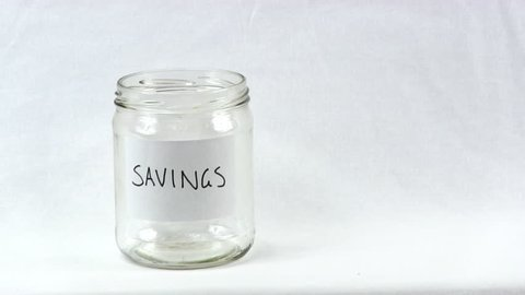Coins dropped into medium sized clear glass jar labeled as savings
