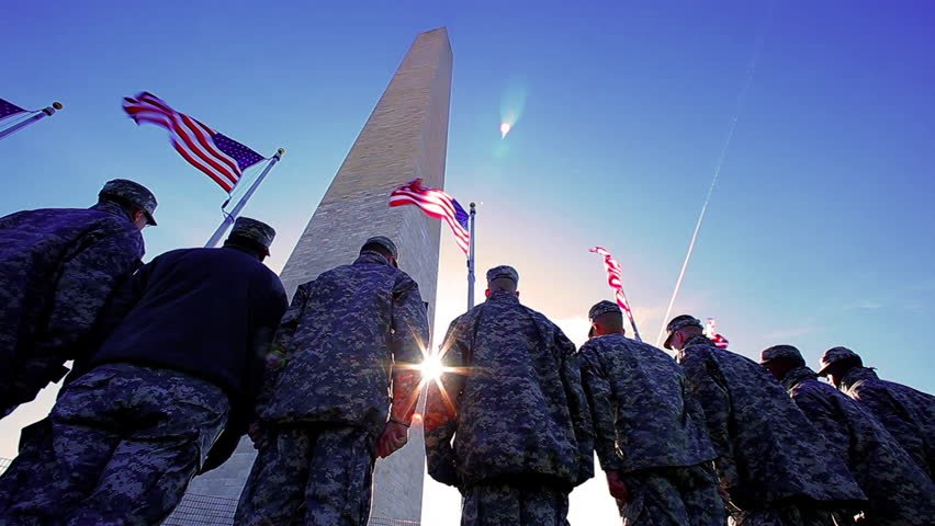 Washington, DC/United States - November 2012: A static shot with a lens flare of the back of a group of soldiers at the Washington monument.