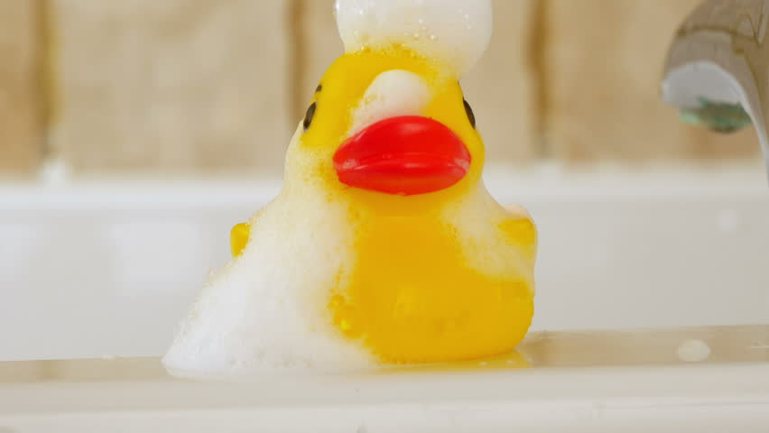 Soap suds running of rubber duck on bath, 4k, UHD