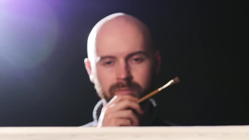 Talanted, bearded, bald artist, painter painting something and evaluates it, brush touchess his lips, doing the final touch on black background, back light, slow motion