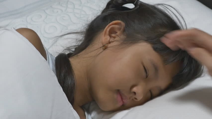 Asian child sick and sleeping on the bed with her mother by her side. | Shutterstock HD Video #9855803