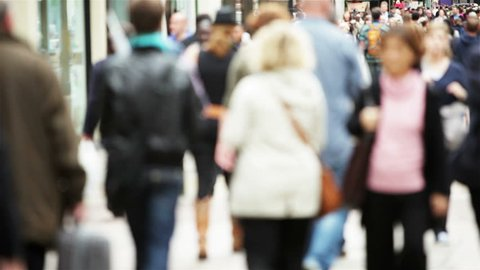 Full frame, video footage of candid and anonymous crowds of shoppers making their way along a busy London retail district.  Intentional defocus.