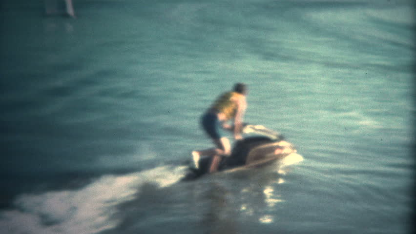 (Super 8 Vintage) Man Attempting to Ride JetSki Fail.  A retro super 8mm reel-to-reel home movie film professional clean and captured in full 4k (3840x2160 UHD) resolution plus footage restoration. | Shutterstock HD Video #9919265