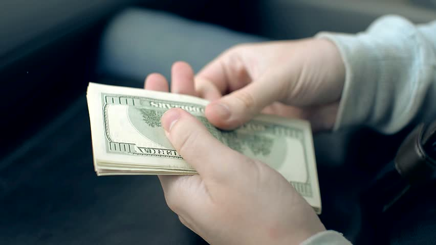 Man counting money. Man recounts money from left to right, front side with the president at the bottom, dollars to the camera turned upside down. | Shutterstock HD Video #9966623